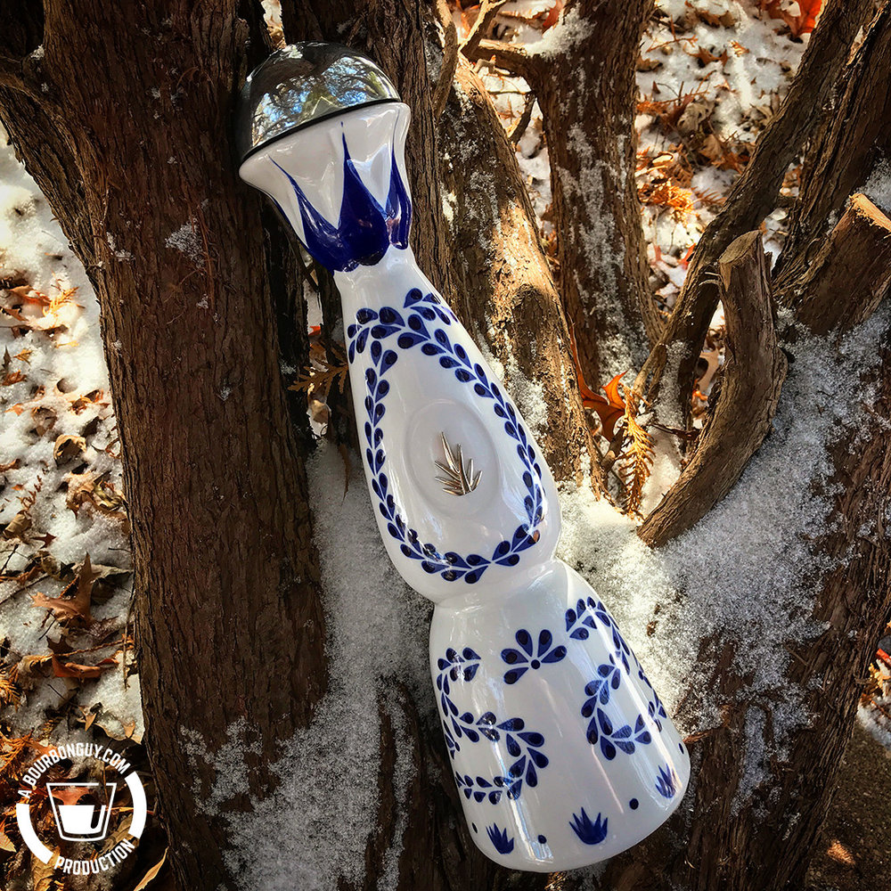 IMAGE: a tequila bottle perched in a tree with snow on the branches and leaves on the ground.