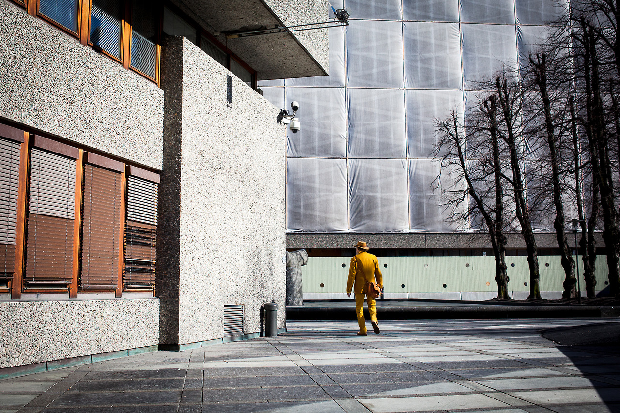 A man in yellow suit walking in the streets of Oslo, Norway.