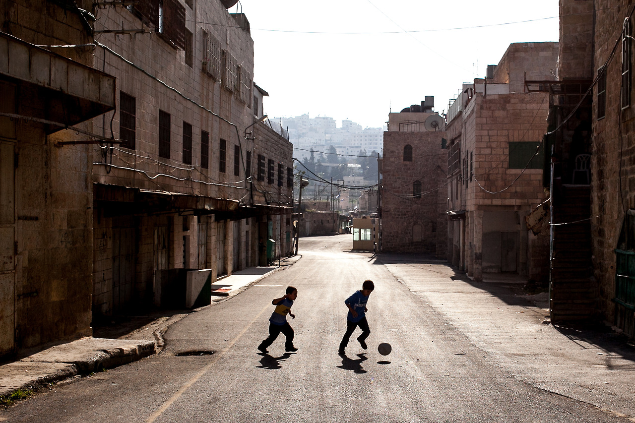 Two Palestinian boys playing at the beginning of Shuhada Street in Hebron. The street is totally closed for Palestinians, and only Israeli citizens are allowed to used the road.