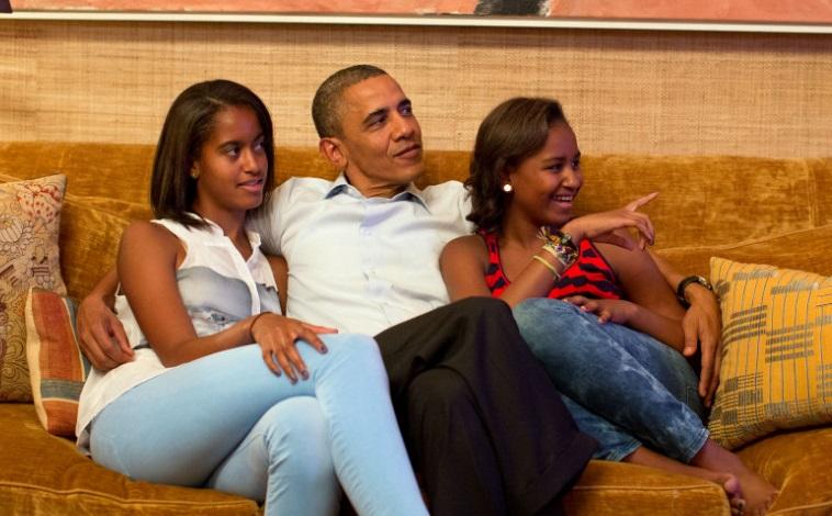 Malia, Barack, and Sasha Obama watching...something. Image courtesy of CNN