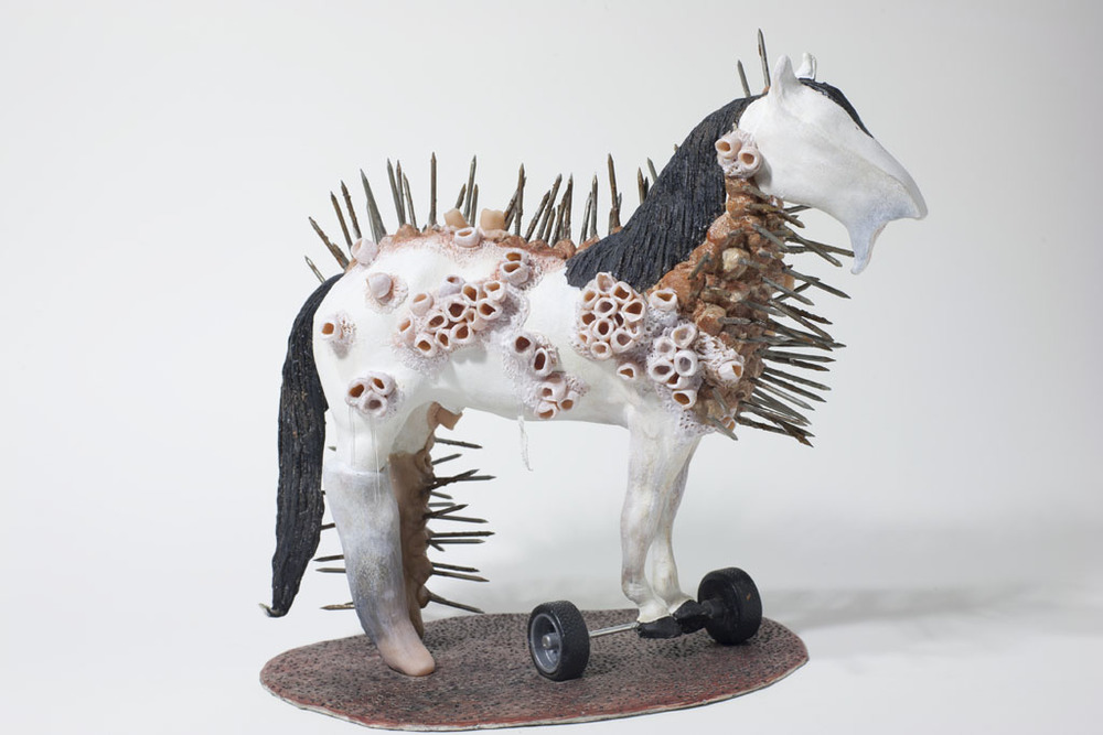 "Baracles and nails, 2014, Mixed Media altered plastic horse, clay, gesso coloured pencil crayon, acrylic, nails, toy wheels, 7"" x 9.5"" x 10"""