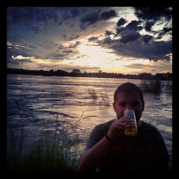 Me drinking a beer on the banks of the Zambezi river.