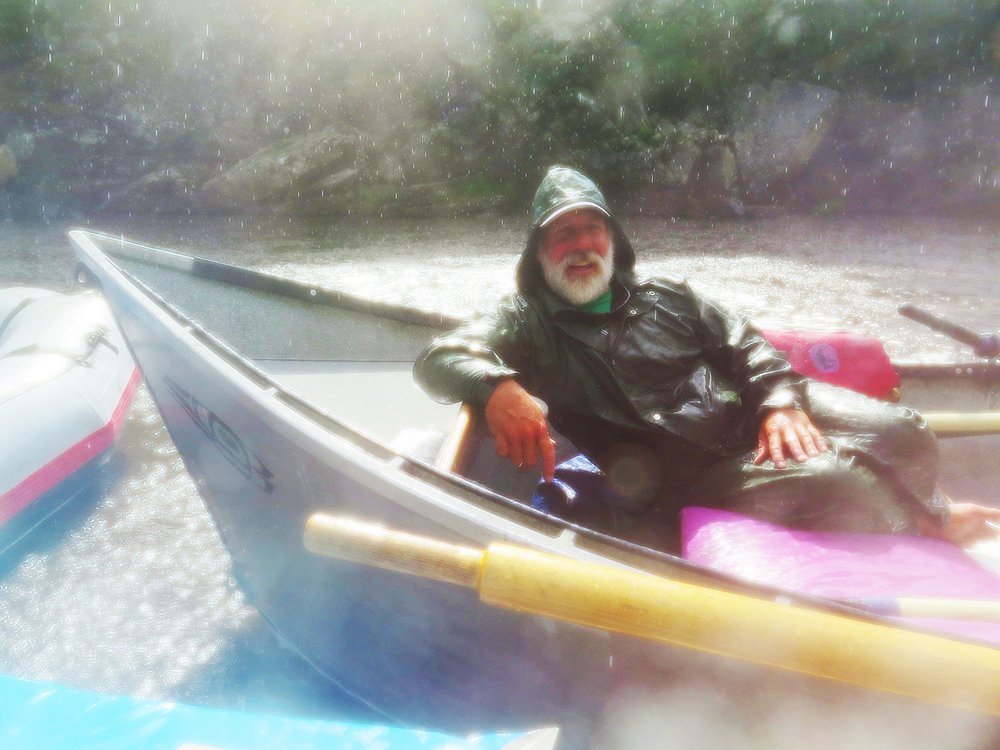 Nine year Middle Fork guide, Roy Akins, reclines in his drift boat, unfazed by a sudden downpour. Roy has been running drift boats for eighteen years and likes the feel of the water below his craft when he's rowing. He lives in Riggins, Idaho with his family where he owns and guides for Rapid River Outfitters.