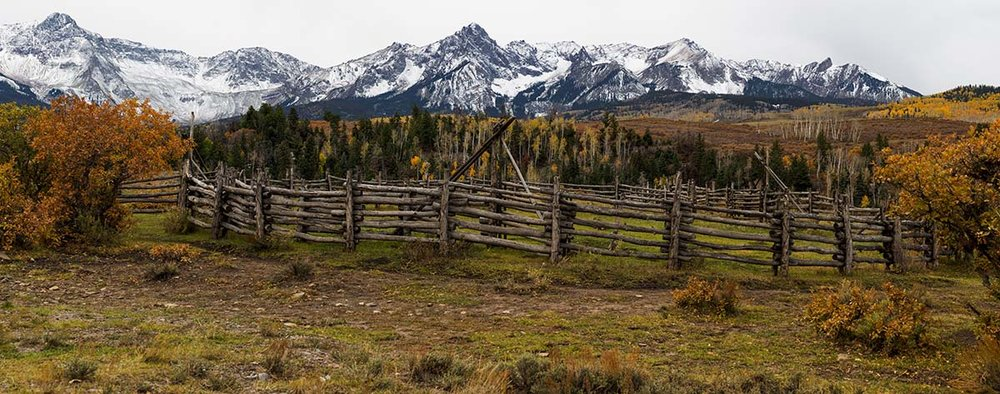 Rustic fence and aspen groves of County Road 9.