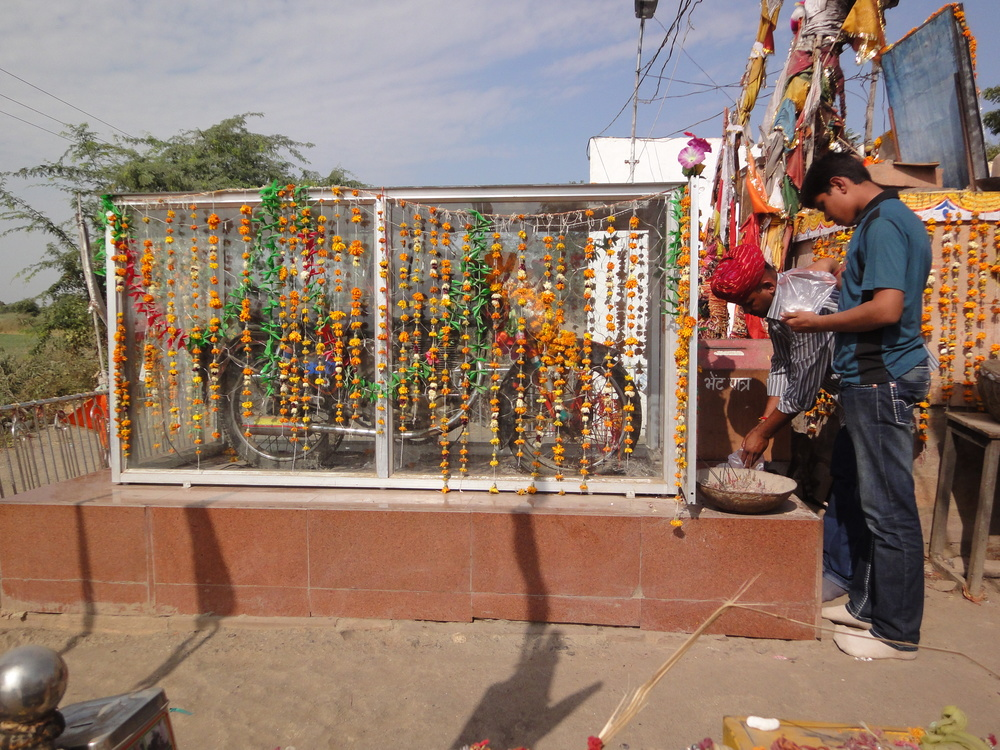 Travellers pay respects and pray to Om Banaji's motorcycle.