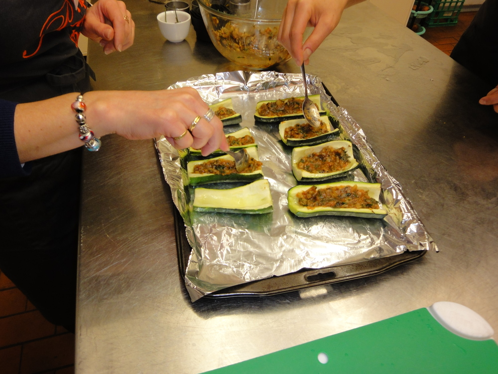 Stuffing the zucchinis before they go in the oven.