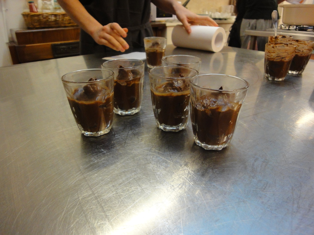Neatening the mousse glasses before they're garnished and served.