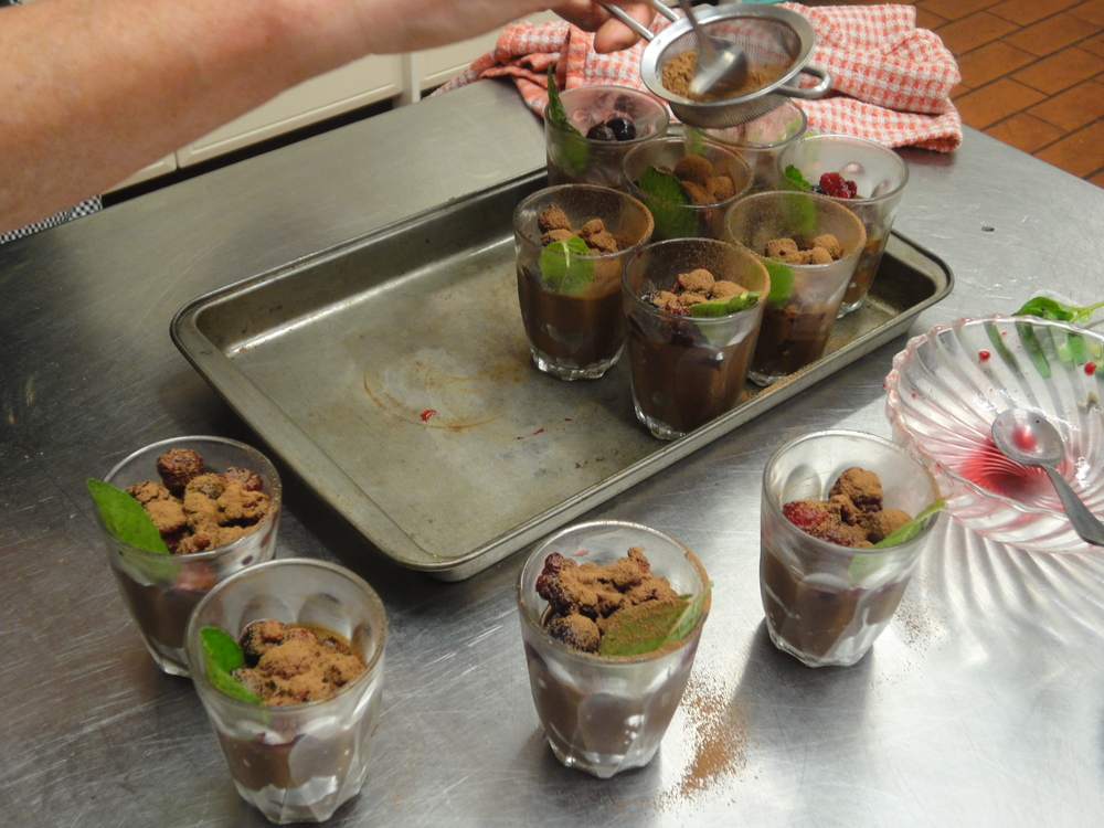 Garnishing our mousse with juicy berries, sprigs of mint and a dusting of cocoa.