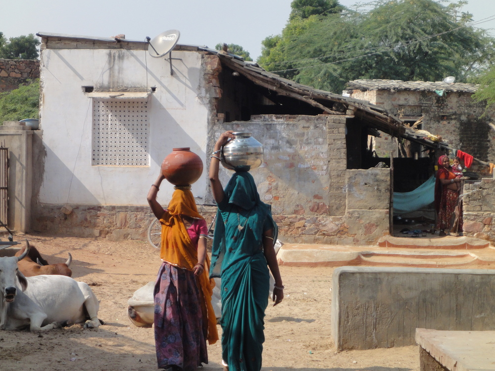 Tordi women carrying water vessels effortlessly. They're covering their faces as a sign of respect.