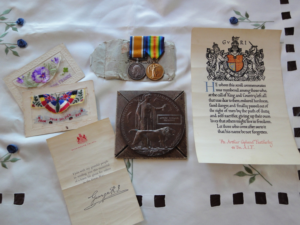 A collection from Arthur's wartime history including a letter from King George V, service medals and postcards he sent home to his family.