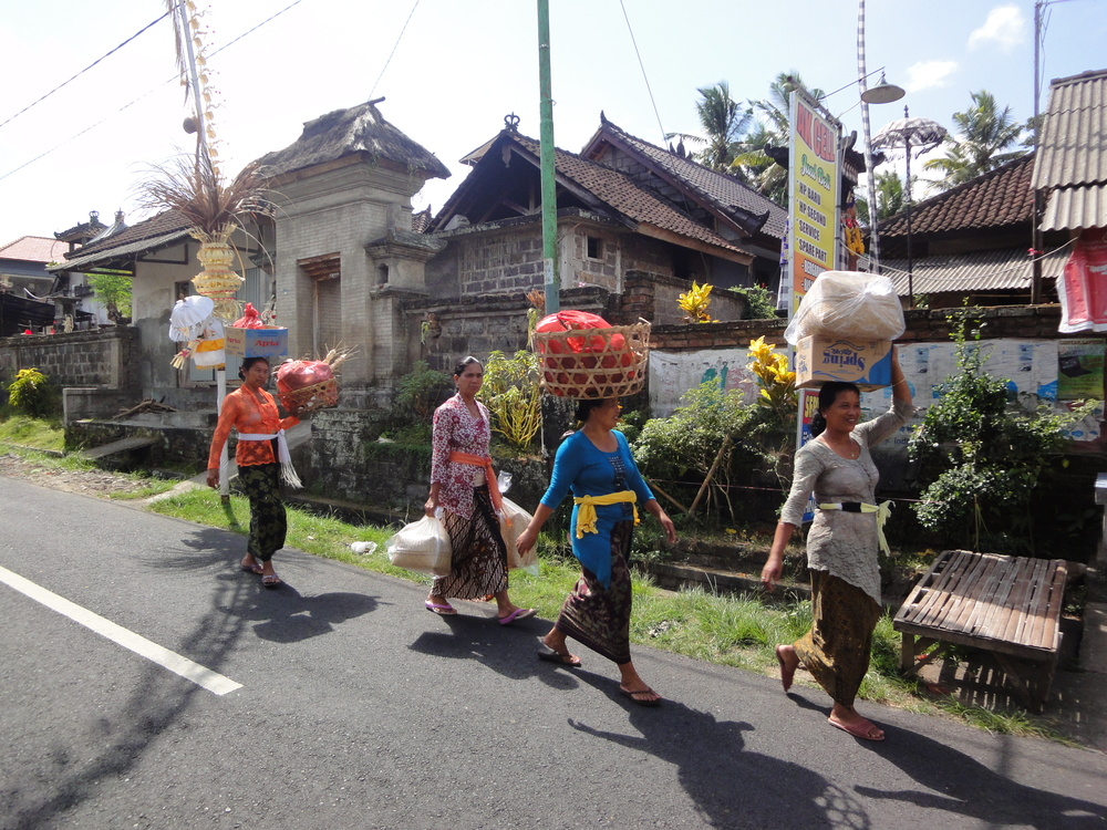 Local women return home after the day's shop, wandering the road under festive penjor decorations.