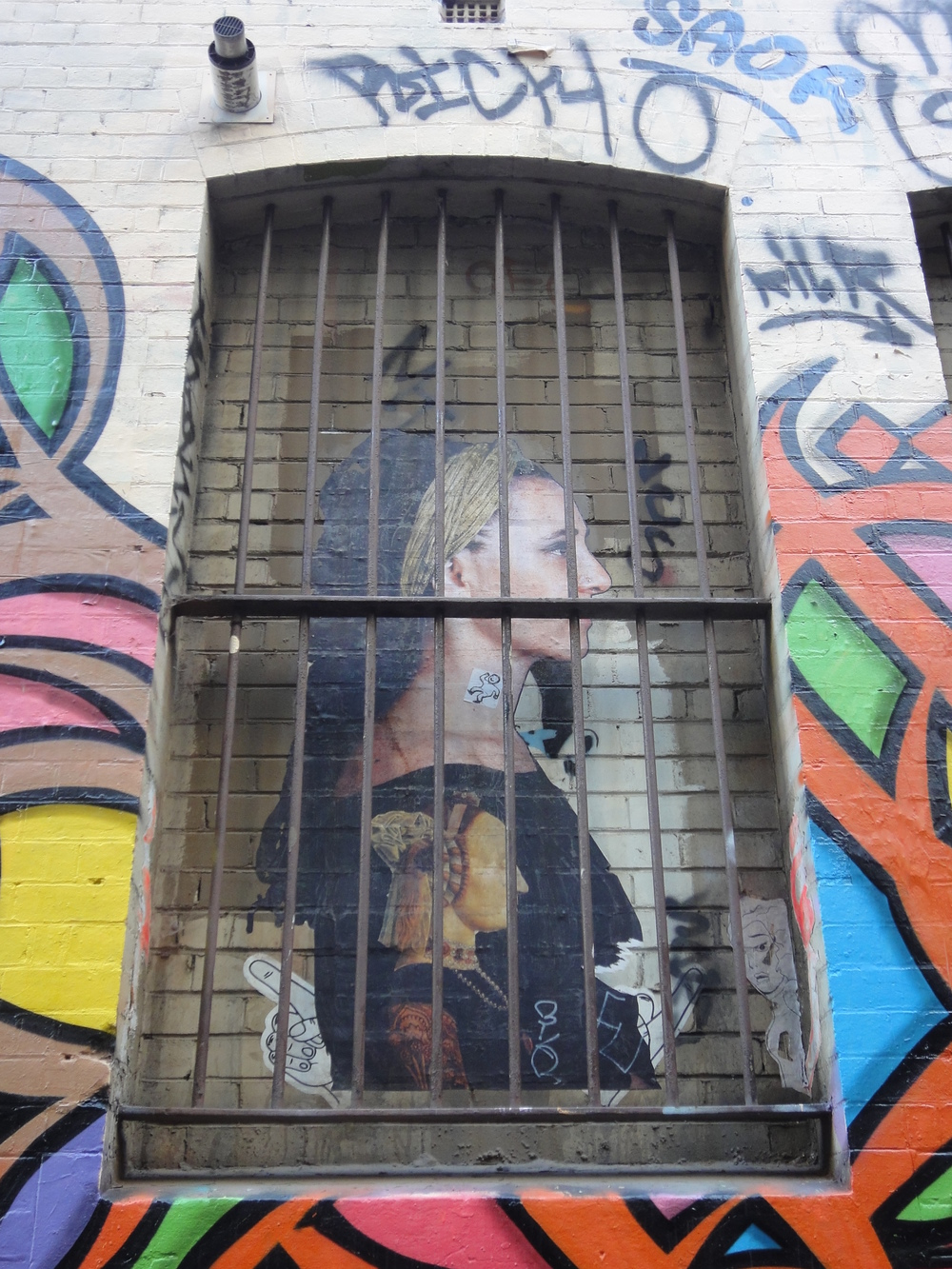 eL Seed's work frames a pastie from another artist featured inMelbourne's Hosier Lane.