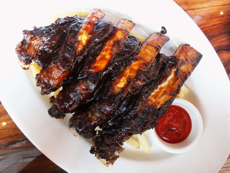 "BBQ Beef Ribs - Rp. 249.900 My order. Only for the hungry ones. USDA ""Choice"" Certified Angus beef. The ribs are succulent enough, but not really that juicy & 'fall-off-the-bone' type. The meat was in fact a tad dry, and needs more of its fingerlickingly good BBQ sauce. Served with Aussie Fries on the BOTTOM. Which makes it messy because when we tuck in to slice the ribs, the fries also got cut off into small messy chunks :(  I've definitely had better rack. Maybe should have ordered its signature steak instead. Nice to try for the big appetite, though."