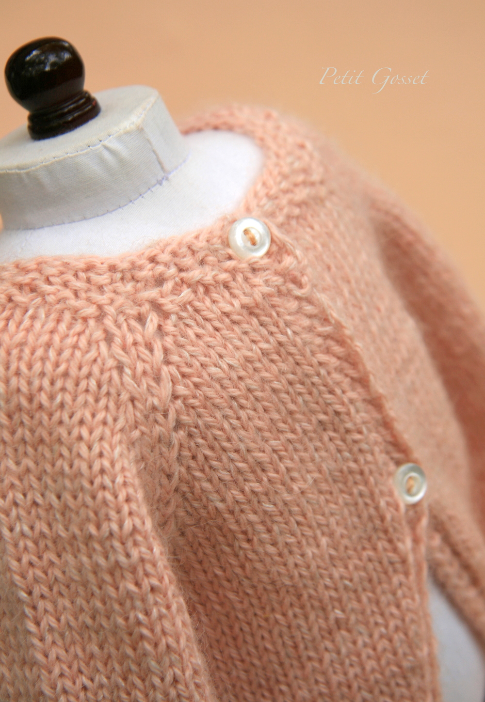 The sweater opens in the back with two little purl buttons