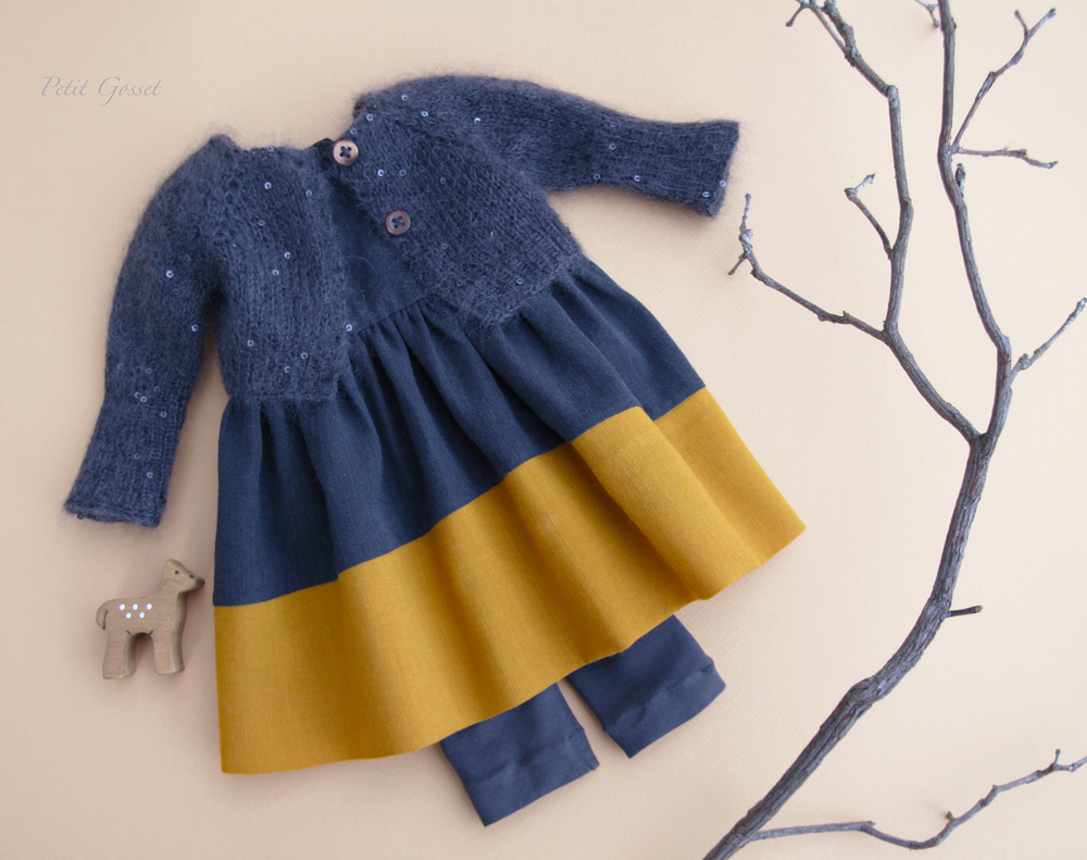 A exquisite wool sleeveless dress, cotton leggings, and a hand-knitted mohair/silk with sequins cardigan. A cute little fawn will come with the set.