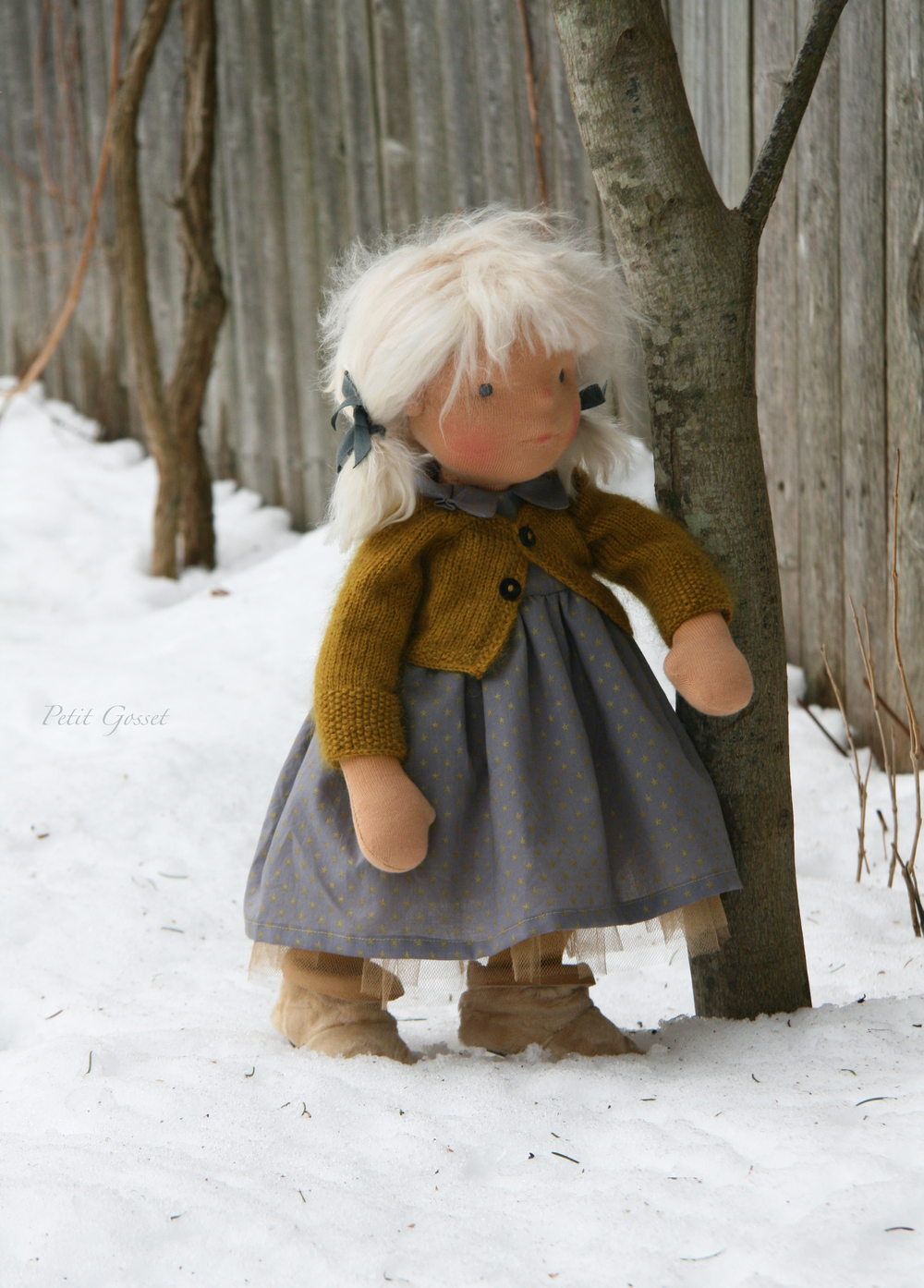 "Malou, about 18"" long, wearing a cotton dress with golden tulle under-layer, hand-knitted cashmere/silk cardigan, long cotton socks, a pair of shearling boots, and silk underwear. by PetitGosset"