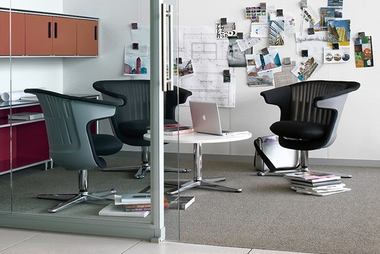 A Steelcase design features casual chairs around a round table. Steelcase