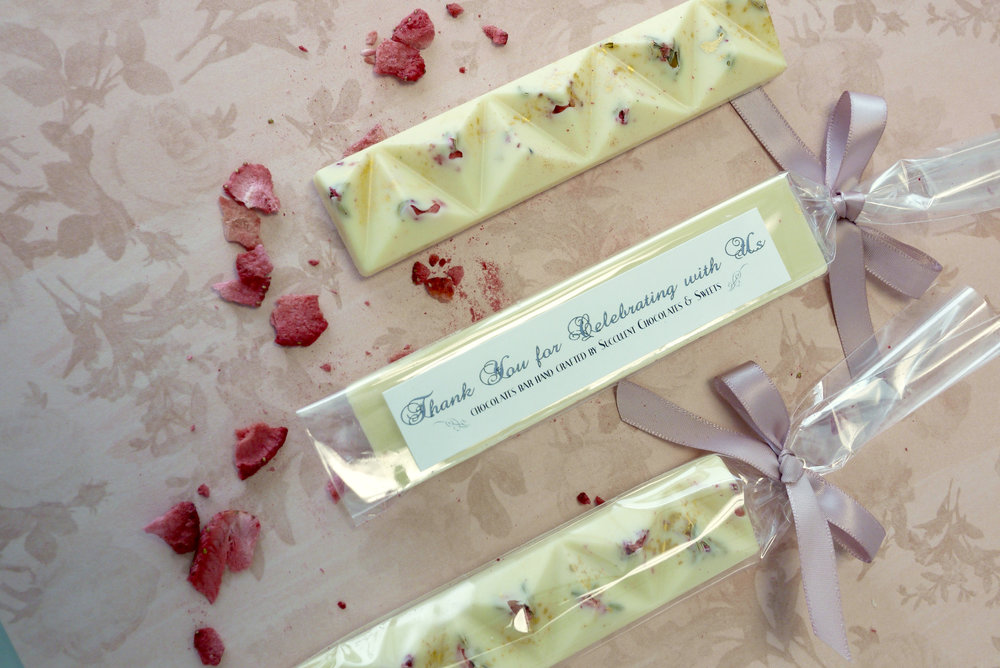This delicate ivory chocolate bar is topped with avourful strawberries, fennel seeds and light dusting of edible gold