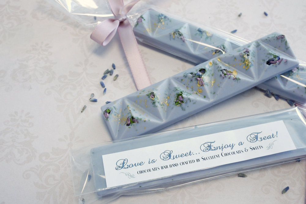 Our exquisite lavender chocolate bar is topped with rich lavender buds, lemon verbena, pink chocolate rocks and a sprinkle of edible gold