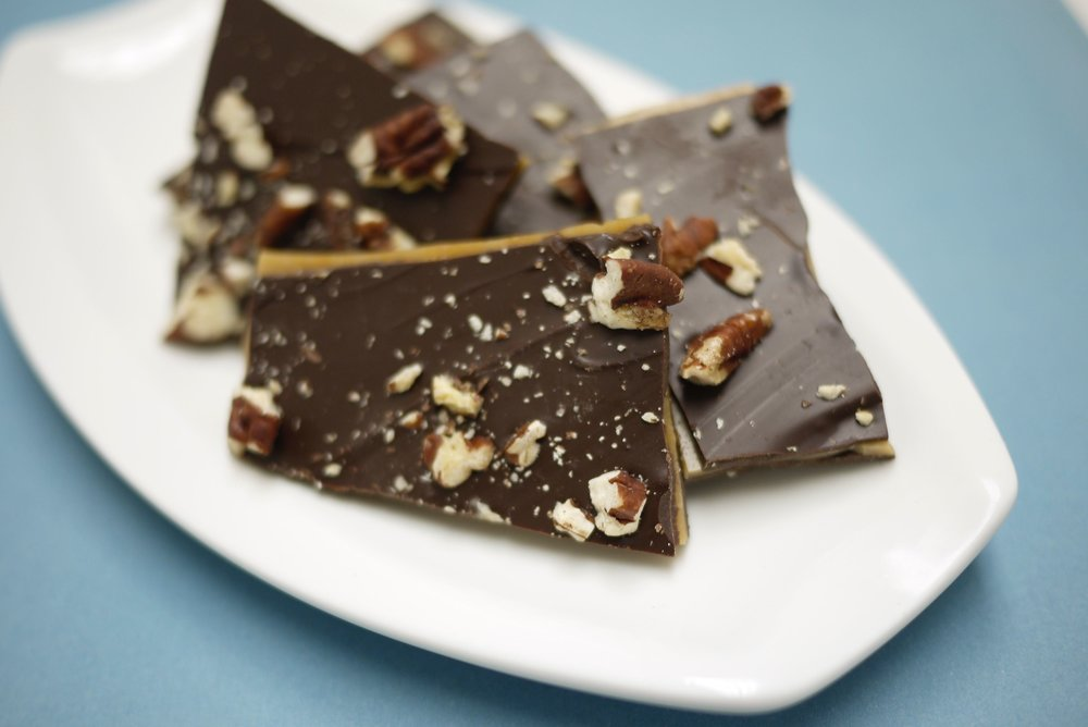 Crunchy Pecan Butter Toffee is handcrafted with creamy butter to achieve the perfect crunch factor. Coated with 54% dark chocolate and pecans.