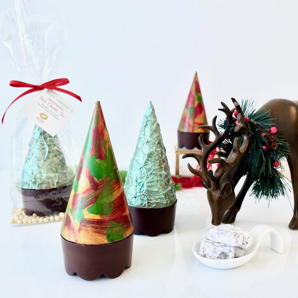 Individual 3D Chocolate Tress  -  Our hand painted 3D trees are a combination of artistry, elegance and flavour. They are individually wrapped in a clear bag, sitting atop of a bed chocolate pearls. Each tree holds a wonderful surprise of 4 mint meltaways.    $12.00