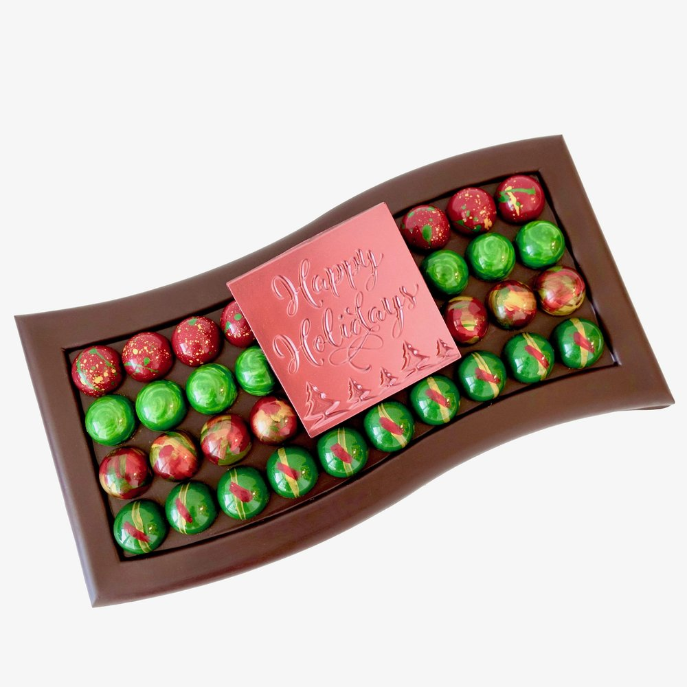 "Chocolate Tray  -  Looking for a gift with that special ""WOW"" factor? This edible dark chocolate tray is topped with 40 hand painted bonbons. Presented in a rigid gift box with a wired bow.  $95.00"