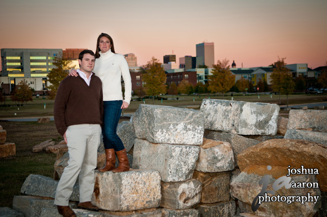 couple in front of the columbia sc slyline at the riverfront park