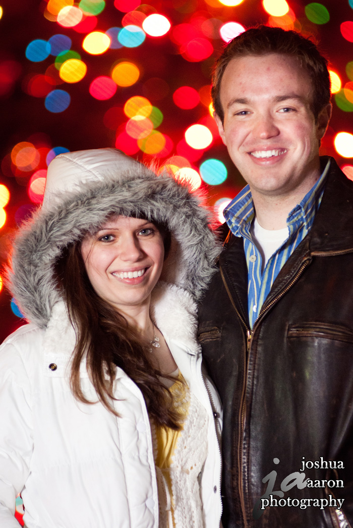 Under the Christmas lights engagement photo with fun colorful bokeh