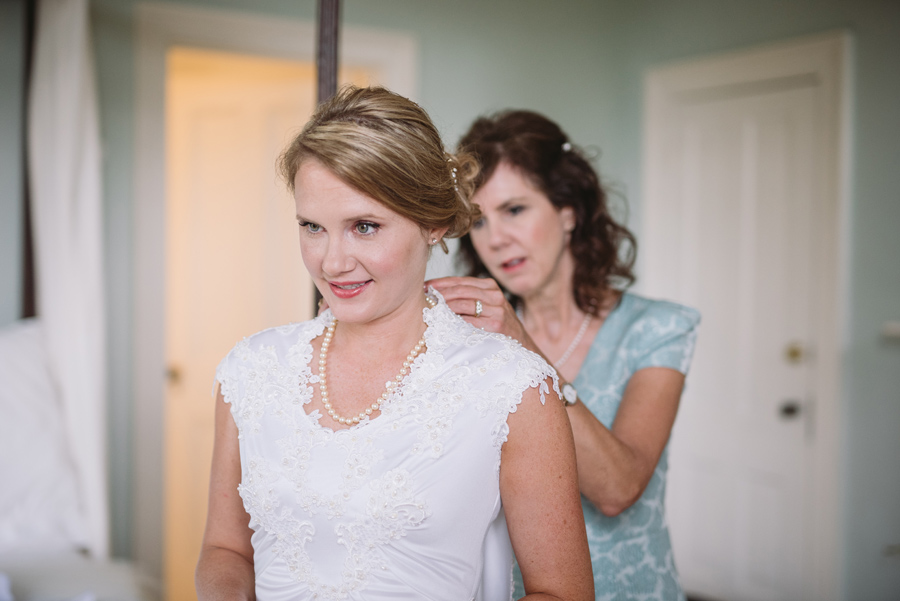 bride getting dressed with mom