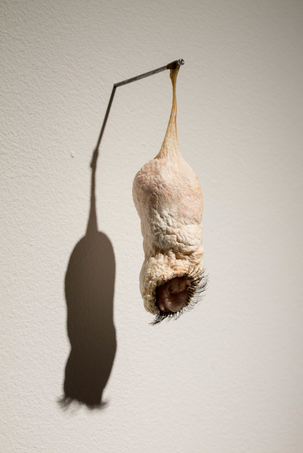 Dangle   - 2013 - beef intestine, fiberglass insulation, and false eyelashes - 6 x 2 x 2 in.