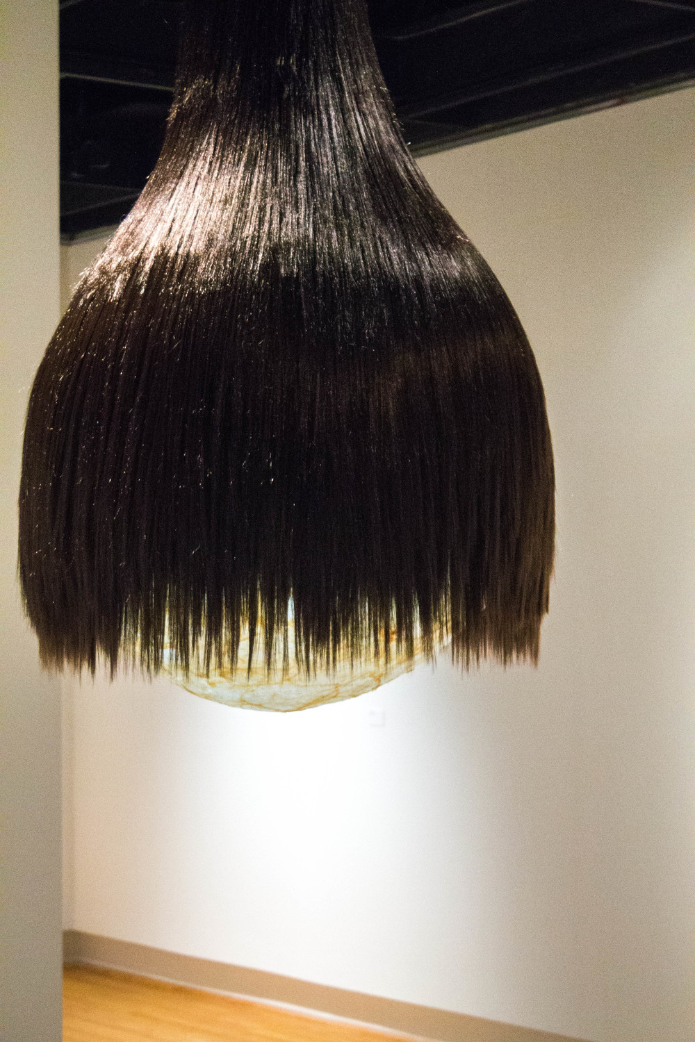 We Can't Pull Ourselves Up To Heaven By The Hair (Samson's Foible)   - 2014 - synthetic hair extensions, fiberglass resin, pork caul fat, cardboard, and light - 8 x 2.5 x 2.5 ft.