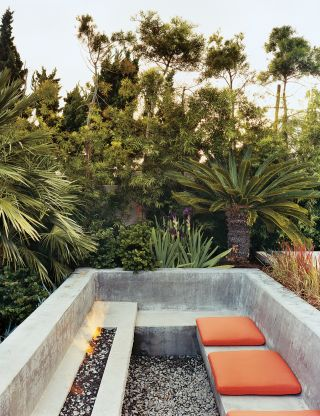 EXOTIC OUTDOOR SPACE IN PALOS VERDES, CALIFORNIA  The sunken outdoor seating area at a Palos Verdes, California, home provides a warm refuge with or without a fire, as even a small amount of sunlight is enough to warm the concrete. The Japanese blood grass's red tips become fiery blades at sunset.   PHOTOGRAPHER:   Raimund Koch    ARTICLE:   The Aquarian,   June 2007    LOCATION:   Palos Verdes, California