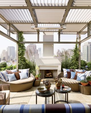 MODERN OUTDOOR SPACE BY DE LA TORRE DESIGN STUDIO  Edward Siegel created the trellis and fireplace for the rooftop terrace, above the master bedroom of a Manhattan apartment. The slate paving is from Stone Source, the daybeds and glass-top tables are by Dedon, and the pillows are made of Sunbrella and Janus et Cie fabrics. The plantings are by Miguel Pons Landscaping and Matthias Kirwald Landscaping.   ARCHITECT:   Cooper, Robertson & Partners    DESIGNER:   De la Torre Design Studio    PHOTOGRAPHER:   Pieter Estersohn    HOMEOWNER:   Drew and Rachel Katz    ARTICLE:   In The Mix,   August 2013    LOCATION:   New York, New York