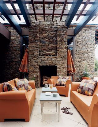 RUSTIC OUTDOOR SPACE BY FISHER WEISMAN  Bubble Club sofas and armchairs from Kartell provide seating on the poolside terrace of an Idaho home.   ARCHITECT:   Jarvis Group Architects    DESIGNER:   Fisher Weisman    PHOTOGRAPHER:   Thomas Loof    ARTICLE:   Don't Fence Me In,   February 2007    LOCATION:   Idaho