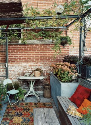 RUSTIC OUTDOOR SPACE BY CARTER SMITH  The roof terrace of photographer Carter Smith's Manhattan home feels romantic thanks to an Iranian tribal rug and throw pillows.   ARCHITECT:   Hottenroth & Joseph Architects    PHOTOGRAPHER:   Martyn Thompson    HOMEOWNER:   Carter Smith    ARTICLE:   Director's Cut,   January 2007    LOCATION:   New York, New York