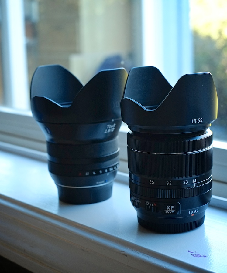 The Zeiss Touit 12mm f/2.8 (Fuji X Mount) in the background compared to the Fuji XF18-55mm zoom in the foreground. About the same length, but features a Zeiss style flare to a significantly wider front element.