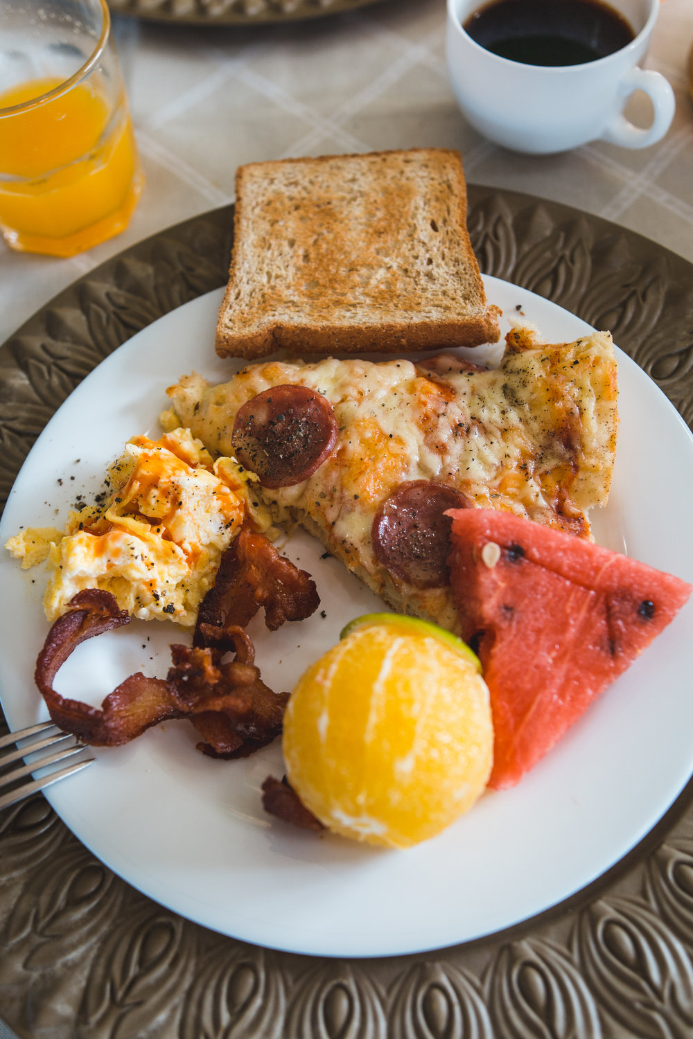 A typical breakfast, with fresh fruit, bacon, breakfast pizza, eggs, and the best coffee and juice on can drink!