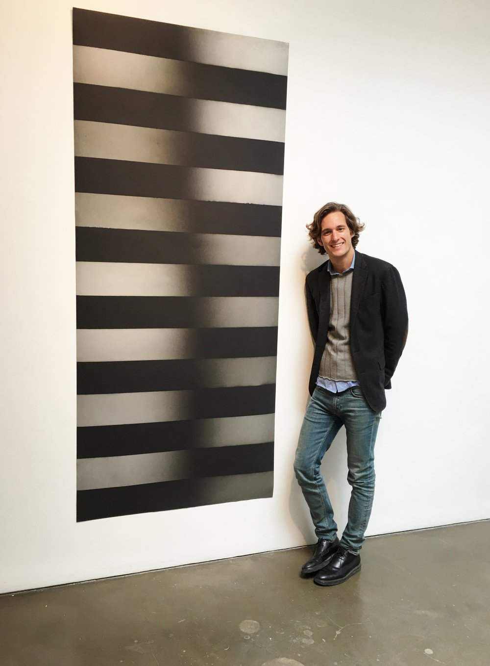 Curator of Whats Up New York, Lawrence van Hagen adjacent to a Larry Bell painting