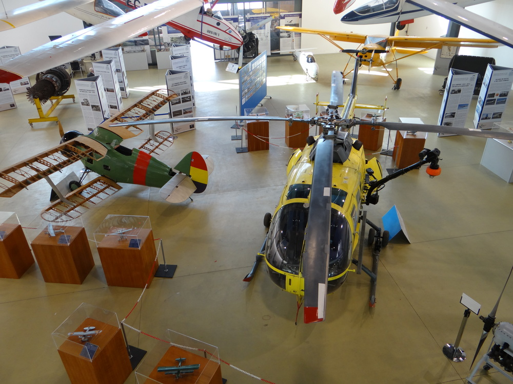The center stage is taken by a bright yellow MBB BO-105 helicopter and a 1930s Polikarpov I-15