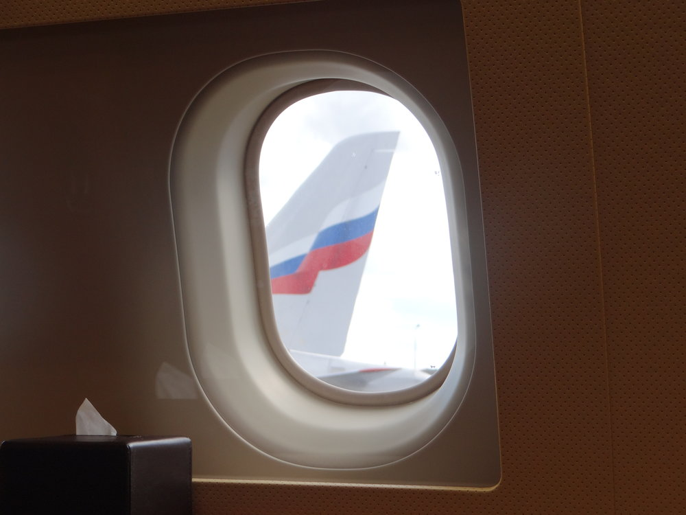 The tail of a Sukhoi Superjet as seen from the window of the Airbus ACJ