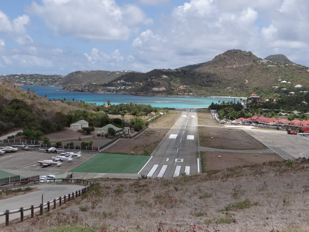 A view of St.Barts airport - landing aircraft have to make a steep descent right after this ridge
