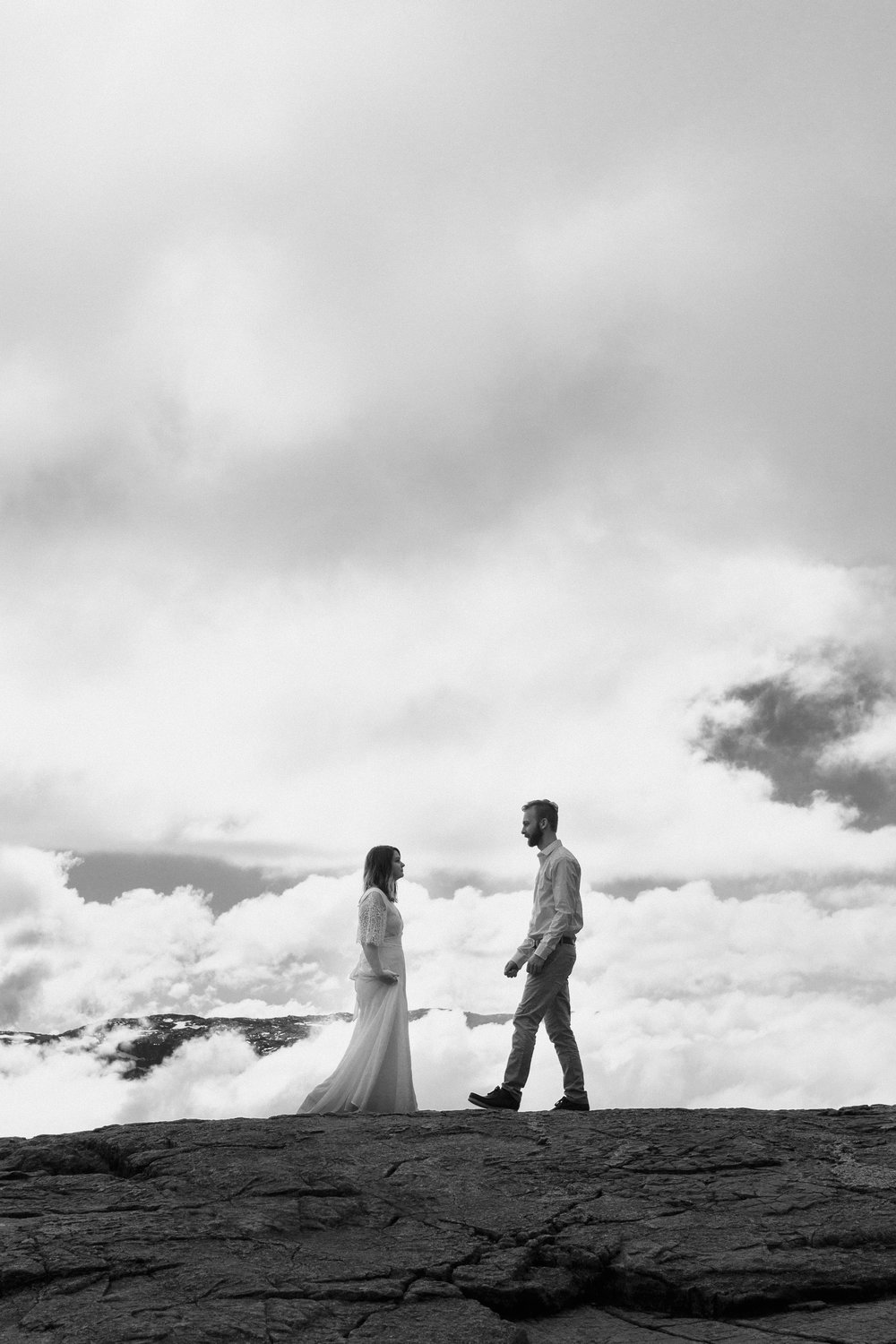 bride and groom walking towards each other on cliff in norway