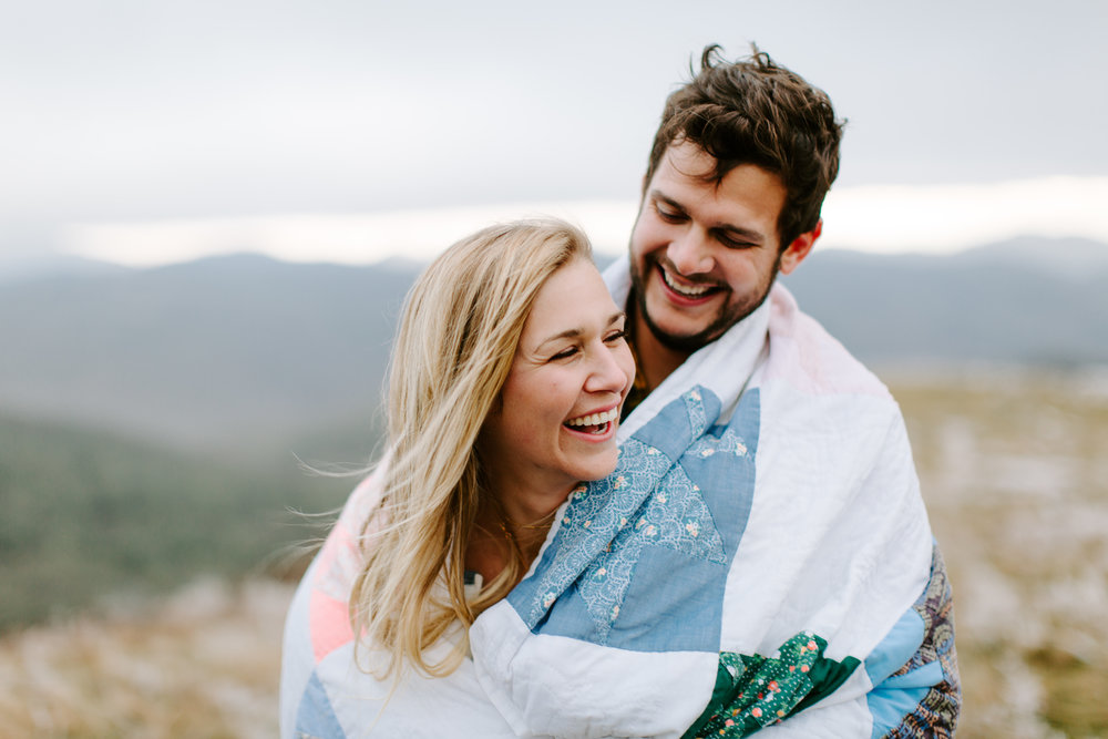 couple wrapped up in blanket on a mountain
