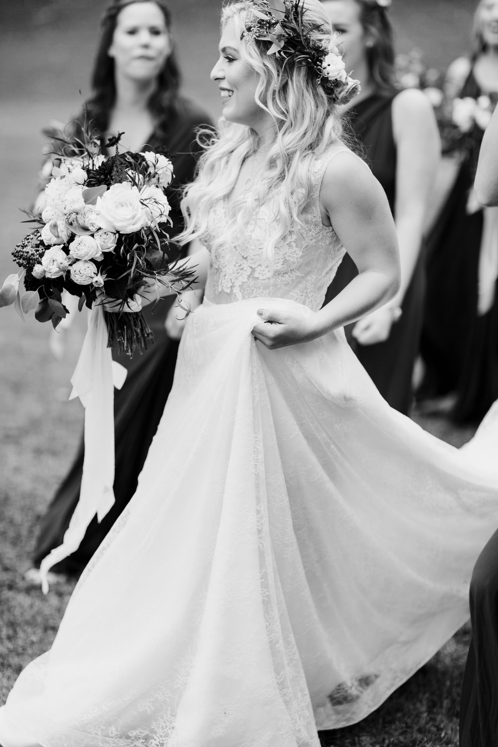 black and white of a bride walking with her bridesmaids
