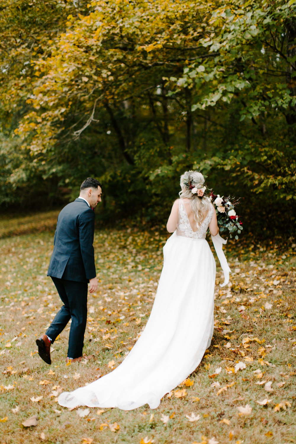 bride and groom in fall leaves