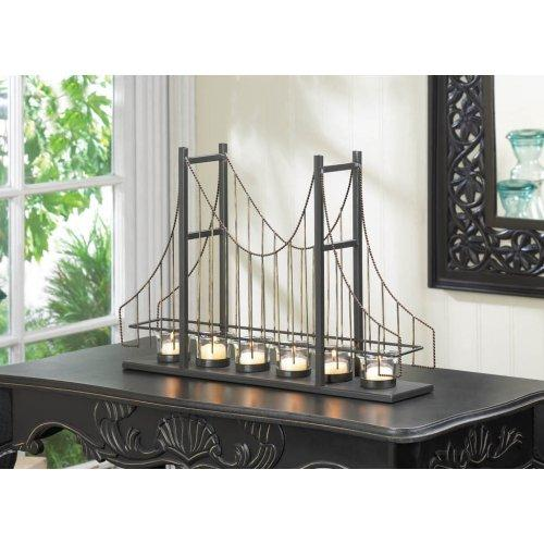 THE GOLDEN GATE BRIDGE MULTI CANDLE HOLDER - A candlelit accessory and a conversation starter, all in one! This charming candle holder features six fluted clear glass candle cups set on the framework of a suspension bridge. Metal posts, golden wires, and beaded details make this a lighting accent that is your room's bridge to style!
