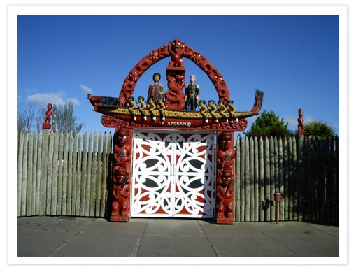 """""""Its carvings depict the history of New Zealand, showing eight warriors paddling a canoe which is representative of all the ancestral canoes at Waitangi in 1840 and, opposite, Captain William Hobson, RN, Governor of New Zealand at that time. This entrance symbolises the Marae as a place for all citizens of New Zealand"""""""