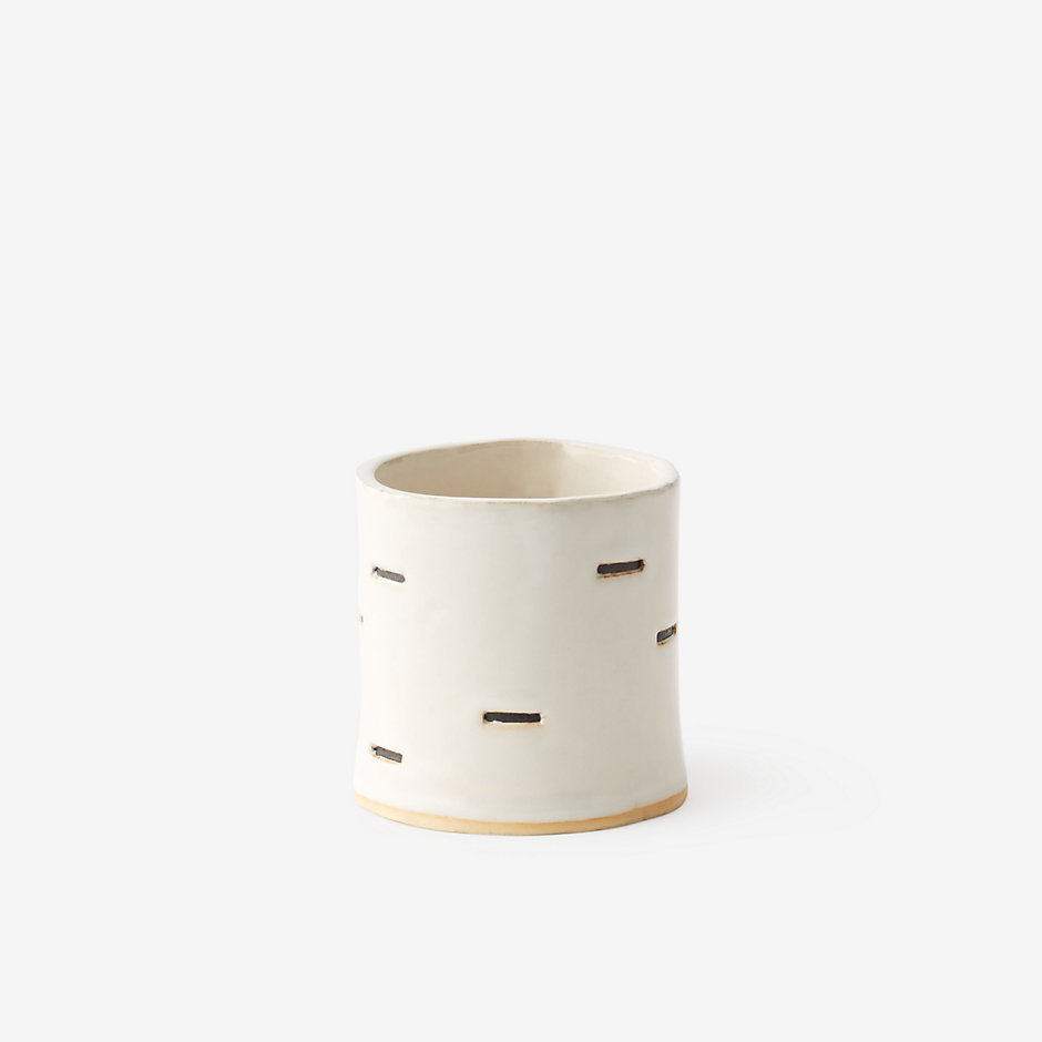 A hand-crafted white clay cup with horizontal line cut-outs and a light overall glaze. AKIKO TSUJI $30