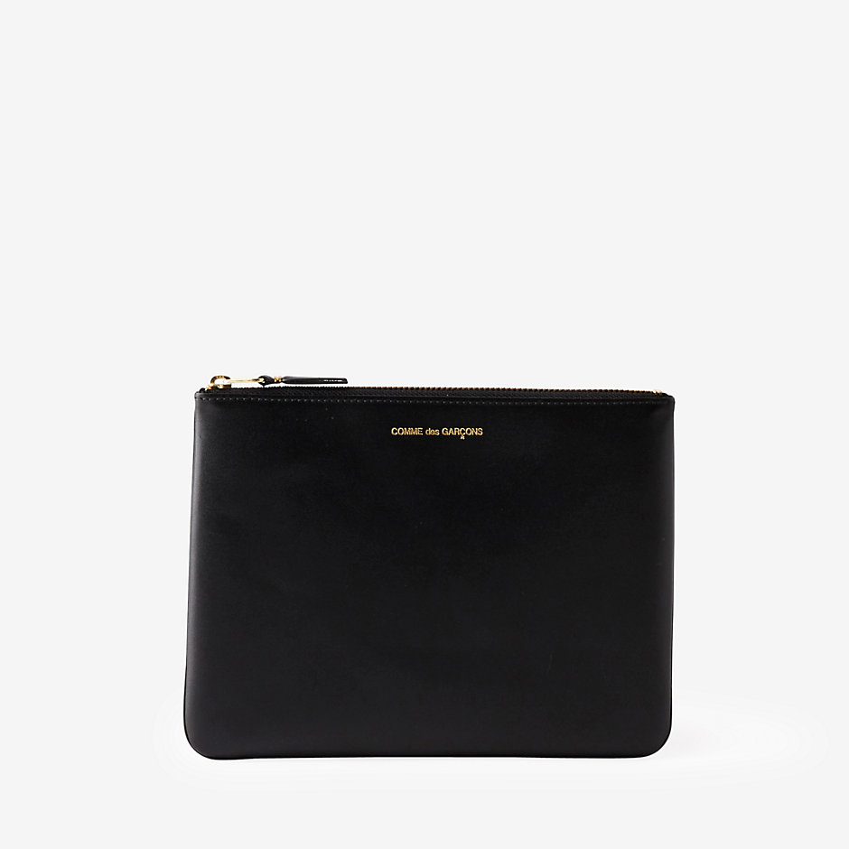 Classic Leather Pouch Black leather zip pouch with single compartment. Sleek and compact clutch to store your phone, keys, and cards. COMME DES GARÇONS $137
