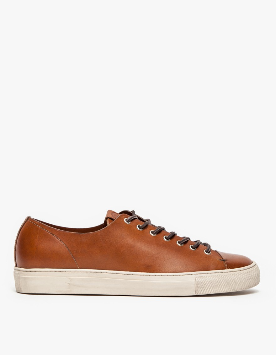 Taino Low Leather Sneaker   A low profile sneaker from Buttero updated with sleek, vegetable tanned leather. Features a cow leather seamed toe, leather laces, nickel finished metal eyelets, padded leather insole with stitching and branded logo on the tongue.  BUTTERO $304